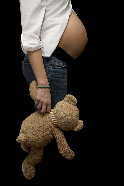 pregnant young woman showing her belly, holding a teddy bear